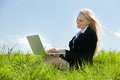 Businesswoman using laptop young sitting in field Royalty Free Stock Photography