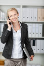 Businesswoman using mobile phone in office portrait of happy Royalty Free Stock Photos