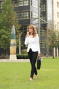 Businesswoman using mobile phone while walking on street full length of a smiling mature talking Royalty Free Stock Photo
