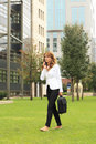 Businesswoman using mobile phone while walking on street full length of a smiling mature talking Royalty Free Stock Photos
