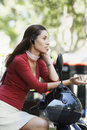 Businesswoman using wireless headset on scooter side view of young while sitting Stock Photo