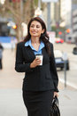 Businesswoman walking along street holding takeaway coffee smiling Royalty Free Stock Photo