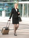 Businesswoman walking in the city with luggage portrait of a Stock Photo