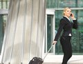 Businesswoman walking with suitcase and talking on mobile phone Royalty Free Stock Photo