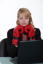 Businesswoman wearing boxing gloves and reading an e mail Royalty Free Stock Photos