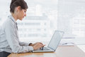 Businesswoman working on her laptop at desk in the office Royalty Free Stock Image