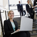 Businesswoman working on laptop on office stairs Royalty Free Stock Photos