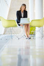 Businesswoman Working On Laptop At Table In Modern Office
