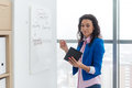 Businesswoman writing day plan on white board, modern office. Side view of caucasian female employee planning schedule