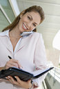 Businesswoman Writing In Planner While On Call Stock Photography