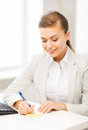 Businesswoman writing on sticky note Stock Photo