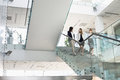 Businesswomen conversing while moving down steps in office Royalty Free Stock Photo