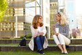 Businesswomen have a break full length portrait of two mature drinking coffee outdoors while they are on coffee Stock Images