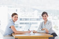 Businesswomen having a meeting at desk and smiling at camera Royalty Free Stock Photo