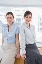 Businesswomen leaning on desk and smiling at camera Stock Photography