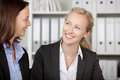 Businesswomen looking at each other happy in office Royalty Free Stock Image