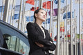 Businesswomen standing near car with flagpoles in background Royalty Free Stock Image