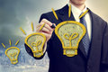 Businness man with idea lightbulbs businessman yellow light bulbs above a big city backdrop Royalty Free Stock Photography