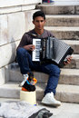 Busker young man playing the accordion with his little dog holding in his mouth a money basket photo taken in lisbon portugal in Royalty Free Stock Image