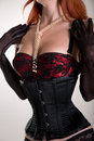 Busty redhead woman wearing corset vintage red br bra and sheer gloves studio shot Stock Image