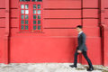 Busy business asian man walking past Red wall. Stock Photography