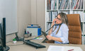 Busy businesswoman talking with cell and fixed line phone in office Royalty Free Stock Photo