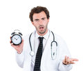 Busy doctor closeup portrait overwhelmed with schedule unhappy male health care professional nurse dentist with stethoscope Stock Photos