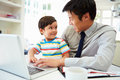 Busy father working from home with son smiling at each other Stock Image