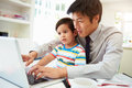 Busy father working from home with son using laptop Stock Photos