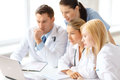 Busy group of doctors looking at laptop computer Royalty Free Stock Photo