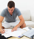 Busy man sitting on couch and writing on paper Royalty Free Stock Photo