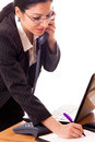 Busy manager woman at her desk speaking on the phone and taking notices Royalty Free Stock Photos
