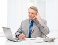 Busy older businessman with laptop and telephone business technologym communication office concept charts coffee in office Stock Photography