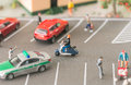 Title: Busy urban life with miniature people and automobiles on a busy street