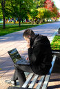 Busy young man laptop sitting bench autumn park talking mobile phone Royalty Free Stock Photography