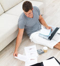 Busy young man sitting on floor and using a laptop Royalty Free Stock Photo
