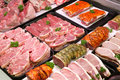 Butchers counter selection of raw meat on trays in a display cooler Royalty Free Stock Photo
