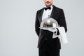Butler in tuxedo and gloves holding silver tray with lid