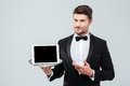 Butler in tuxedo holding and pointing at blank screen tablet Royalty Free Stock Photo