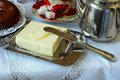Butter in the butter dishand and knife on a white tablecloth Royalty Free Stock Photography