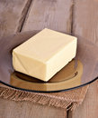 Butter on glass plate wooden table Stock Photo