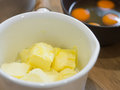 Butter in whte pot and yolk egg on wooden table Royalty Free Stock Photo