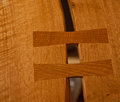 Butterfly key joint fine woodworking installed to stabilize a crack in a long wooden table Stock Images