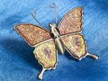Butterfly trinket on blue fabrics shiny shaped jewelry in background Stock Photos
