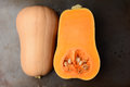 Butternut squash on a metal cooking sheet the fruit is cut in half showing both the inside and outside horizontal format Stock Photography