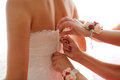Buttoning wedding dress bridesmaids with flowers Stock Photography