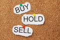 Buy hold or sell the words and pinned to a cork notice board these are investment decisions when we trade stocks and shares in the Royalty Free Stock Photos