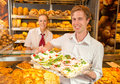 Buyer in bakery presenting tray with sandwiches customer full of Stock Images
