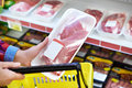 Buyer chooses meat in supermarket