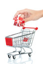 Buying christmas presents woman hand putting down present into shopping trolley isolated on white conceptual image Royalty Free Stock Image